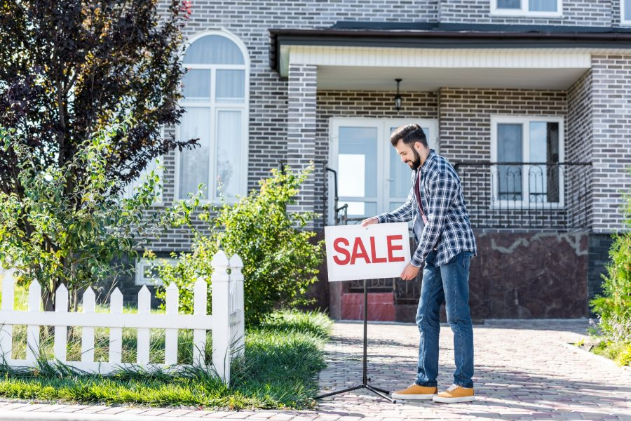 young man with sale board selling his new house